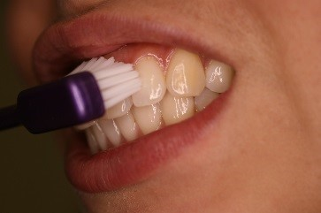 Teeth brushing technique for a healthy smile with a manual toothbrush with medium to soft bristles